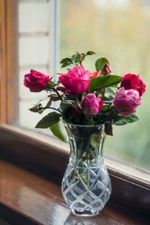 Homemade roses. Bouquet in a crystal vase on a wooden window. The concept of quiet and cozy village life, gardening and environmental friendliness