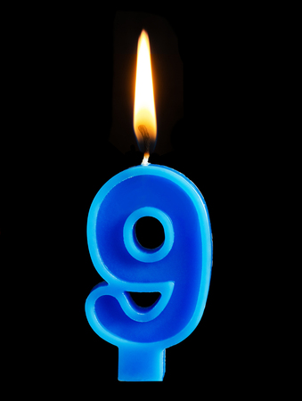 Burning birthday candle in the form of 9 nine figures for cake isolated on black background. The concept of celebrating a birthday, anniversary, important date, holiday, table setting