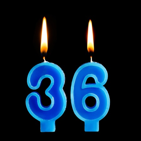 Burning birthday candles in the form of 36 thirty six for cake isolated on black background. Foto de archivo