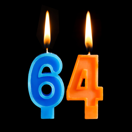 Burning birthday candles in the form of 64 sixty four for cake isolated on black background.