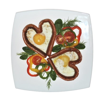 Valentines day breakfast - grilled heart-shaped sausages with eggs and slices of multi-colored peppers, cherry tomatoes and herbs
