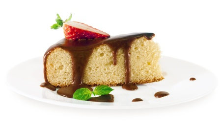 A piece of sponge cake with chocolate sauce,strawberry and mint on a white plate on white isolated background  Stock Photo