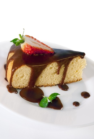 A piece of sponge cake with chocolate sauce,strawberry and mint on a white plate on white isolated background