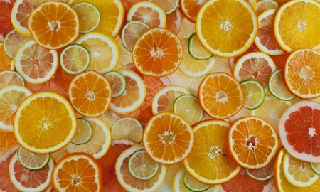 Background with citrus-fruit of pomelo, grapefruit, orange, lemon, mandarin and lime slices   Stock Photo