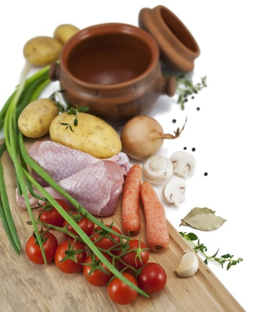 Ingredients for a roast chicken in a pot   chicken, potatoes, carrots, tomatoes, onions, mushrooms, garlic, black pepper and bay leaf  Isolated on white    Stock Photo