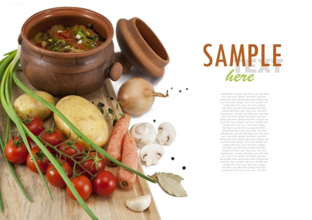 Roast in a pot and ingredients  potatoes, carrots, tomatoes, onions, mushrooms, garlic, black pepper and bay leaf  With sample text   Isolated on white