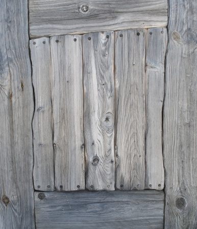 Part of the ancient doors of the old gray weathered knotted wood