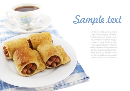 Sausage in the dough on a plate and cup of tea on white isolated background  with sample text Stock Photo