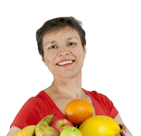 A happy smiling middle-aged woman holding a basket full of fruits  Isolated over white