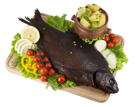 Smoked bream on a wooden board with a hot potato in a clay pot, tomatoes, lettuce, slices of lemon and yellow paprika, onion and dill  Stock Photo