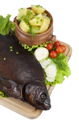 Smoked bream on a wooden board with a hot potato in a clay pot, tomatoes, lettuce, onion and dill  photo