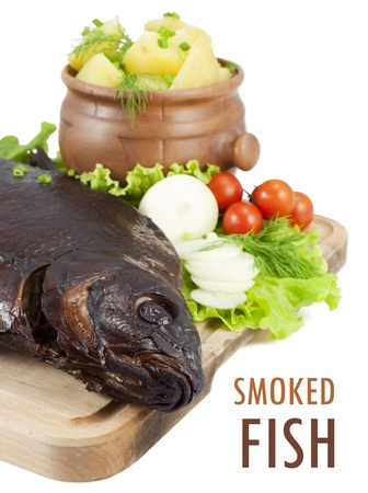 Smoked bream closeup on a wooden board with a hot potato in a clay pot, tomatoes, lettuce, onion and dill