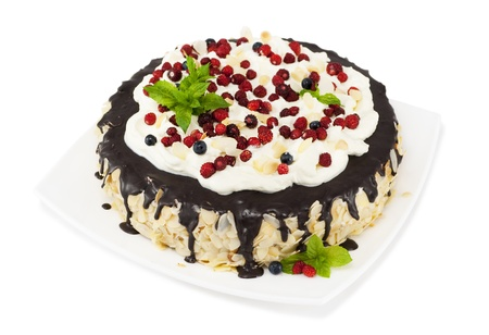 Chocolate cake with chocolate icing, whipped cream, wild strawberries, blueberries and mint leaves
