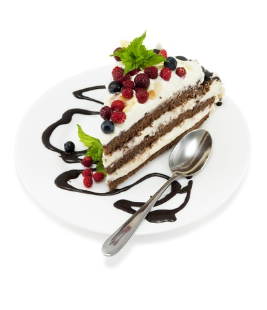 Piece of chocolate cake with chocolate glaze, whipped cream, wild strawberry and  blueberries on white isolated background