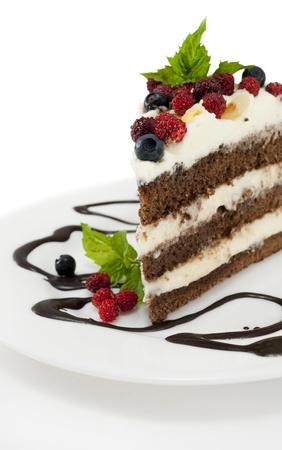 rebanada de pastel: Trozo de pastel de chocolate con glaseado de chocolate, crema batida, fresas silvestres y ar�ndanos en fondo blanco aislado