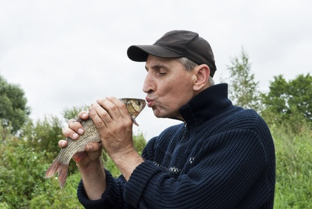 A lucky fisherman kiss a chub Stock Photo