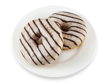 Two donuts with icing on a white plate isolated on white Stock Photo