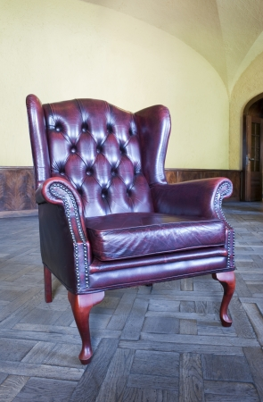 Old vintage red leather chair in the interior