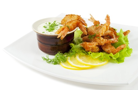 breading: Fried prawns in coconut breading with dipping sauce on a white plate  on white isolated background  Stock Photo