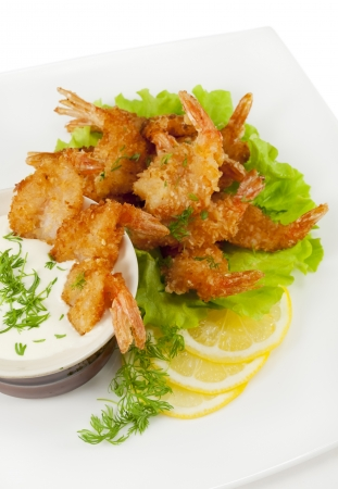 breading: Fried prawns in coconut breading with dipping sauce on a white plate