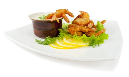 Fried prawns in coconut breading with dipping sauce on a white plate  on white isolated background  Stock Photo