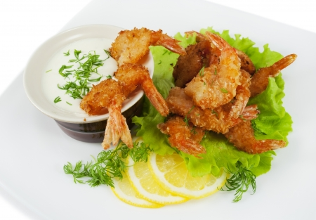Fried prawns in coconut breading with dipping sauce on a white plate