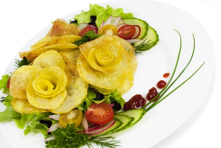 French fries in the form of a rose on a plate with a salad on white isolated background