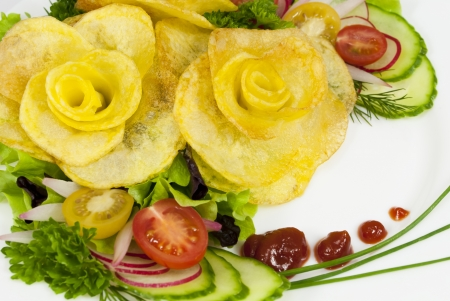 French fries in the form of a rose on a plate with a salad, cherry tomatoes, cucumber and dill Stock Photo