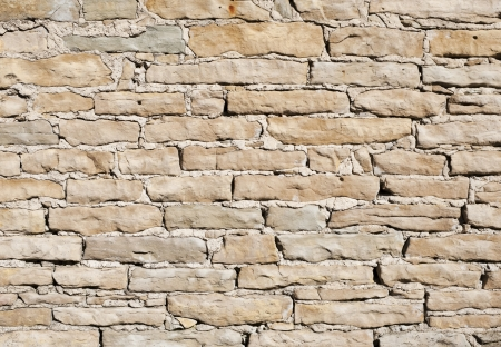 Limestone wall on a bright sunny day as background