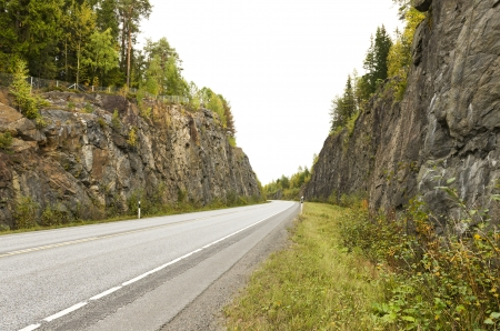 Highway among granite rocks in early autumn   Autumn landscape
