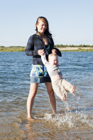 Young beautiful mother plays with the small child on the bank of the lake Stock Photo