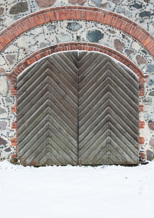 Old wooden gate with pig-iron rivets in a granite wall in the winter photo
