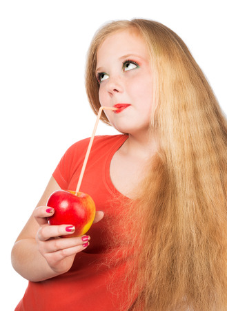 Attractive teen girl in the orange t-shirt holding an red apple in her hand  Face closeup over white isolated background  Stock Photo