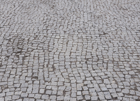 Street  cobbled by granite stones as background, texture photo