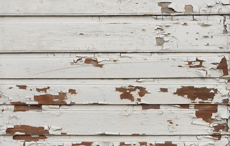 Wooden wall with white paint is severely weathered and peeling as background Stock Photo