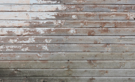 Old wooden wall with white paint is severely weathered and peeling as background