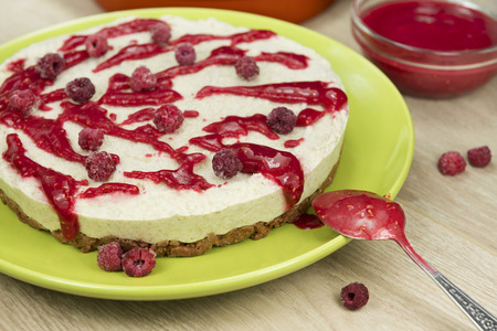 Raw vegan berry cheesecake gluten-free with the frozen raspberry and raspberry sauce on a bright wooden background. Fully raw food.