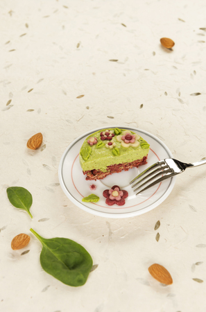 Raw vegan spinach cake with the raw marzipan flowers and leaves on a bright nature paper background. Fully raw food.