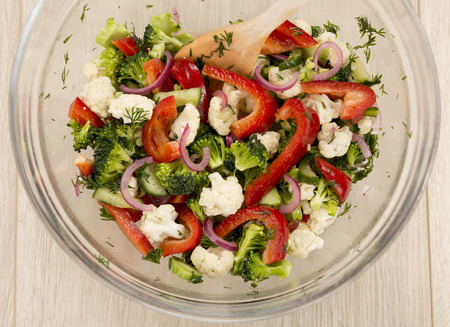 Fresh vegetable salad with broccoli, cauliflower, marinated cucumbers, marinated red onions, sweet red pepper and dill. Fully raw food. Stock Photo