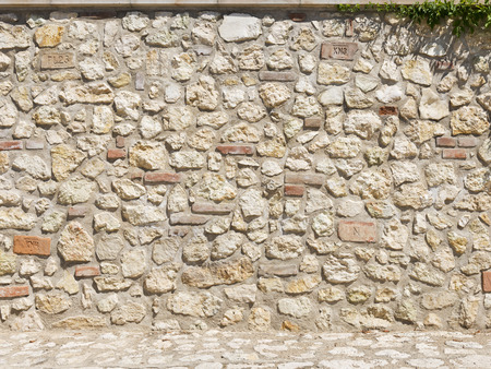 Picturesque stone and brick wall in a bright sunny day as background Stock Photo