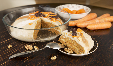 Slice of raw vegan carrot cake with walnuts and dates. Healthy food, dessert. Old vintage dark table surface as background.