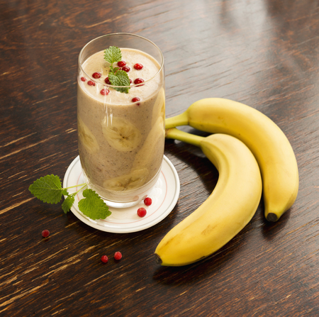 Healthy frozen cowberry and banana smoothie with mint on old vintage table.