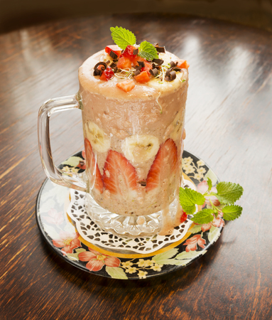 Healthy fresh strawberry and banana smoothie with lucerne sprouts, strawberry pieces, chocolate and mint on old vintage table.
