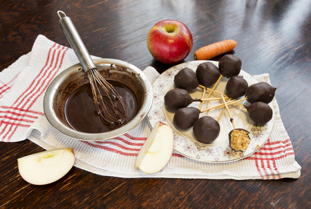 Healthy raw apple and carrot candies on sticks in raw chocolate on old vintage table.