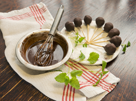 Healthy raw mint candies on sticks in raw chocolate with mint on old vintage table.