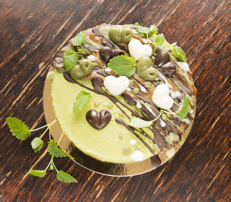 Raw vegan mint cake with nuts, decorated with  raw chocolate hearts and leaves of a melissa Stock Photo
