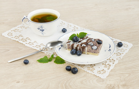 The piece of raw vegan blueberry cake decorated with melissa leaves Stock Photo