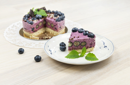 The piece of raw vegan blueberrycake decorated with melissa leaves