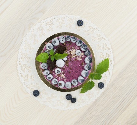 Raw vegan blueberry cake decorated with melissa leaves on the light wooden surface Stock Photo