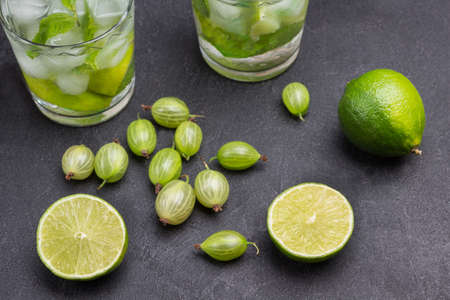 Slices of lime and gooseberries on table. Two glasses of cold drink with lime, mint and ice. Black background. Top view Stock Photo